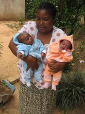 Photo of Pauline holding rescued twin babies