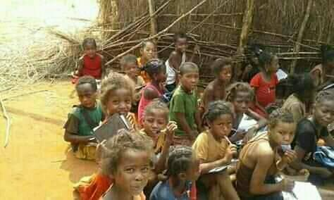 Photo of children in SW Madagascar stting on the ground with pencils and notebooks